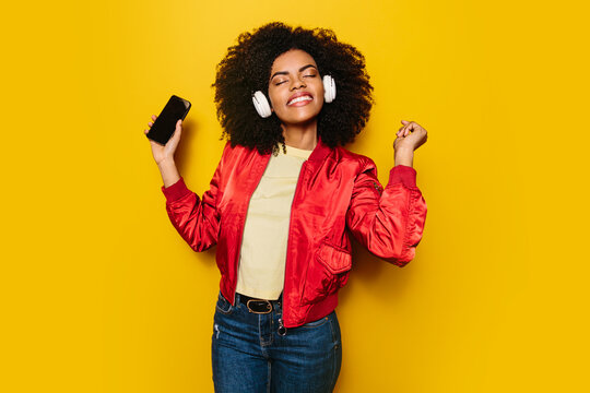 Beautiful afro woman listening to music with white headphones and cellphone