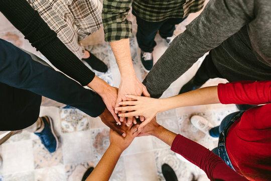 Crop people stacking hands in unity spirit