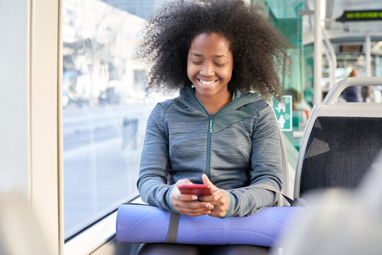 Cheerful sporty woman using phone in bus