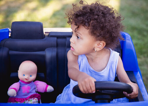 Pretty toddler girl with curly hair sitting in her toy car with her baby doll