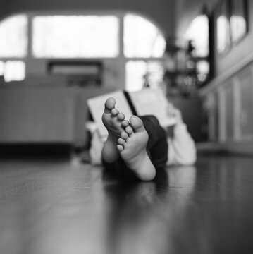 Young girl laying on hardwood floor reading a book with only her feet in focus.