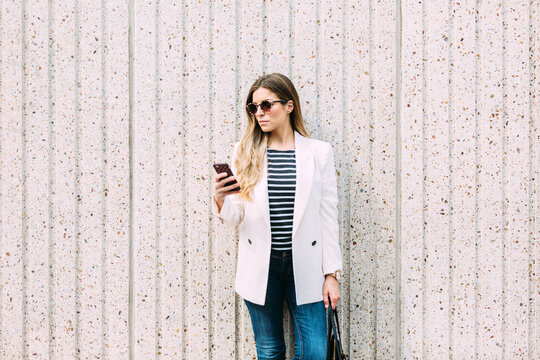Businesswoman texting on cellphone near a white wall