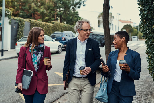 Diverse colleagues walking on street and talking