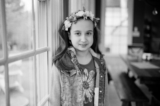 Black and white portrait of a young girl wearing flowers in her hair