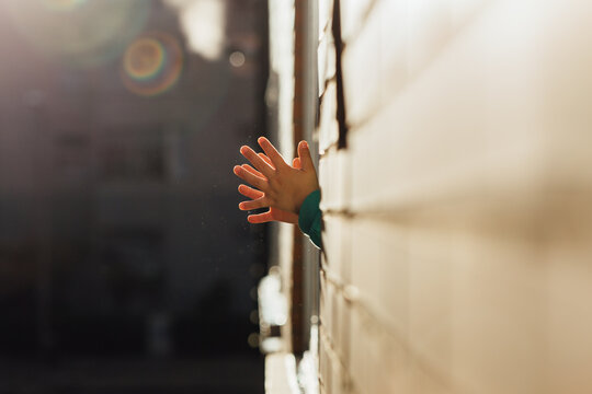 Unrecognizable little boy applauding in his window in gratitude to the health personnel and other groups during the confinement for the coronavirus