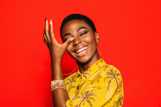 Beautiful Afro Woman posing over red crying of laughter background smiling with eyes closed