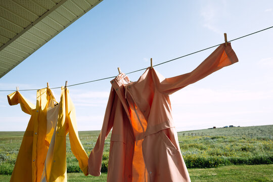 Two raincoats drying on a rope outdoors