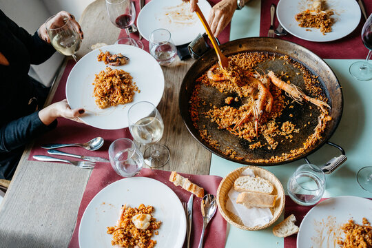 Family dinner with seafood paella and wine