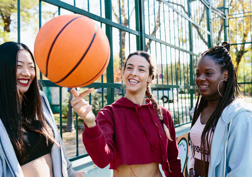 Three women looking at a basketball balancing on a woman's finger