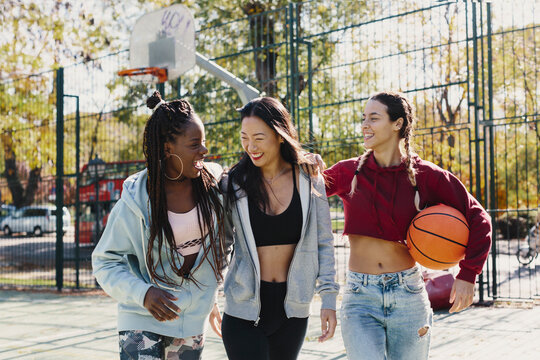 Multi ethnic group of friends with basketball ball hanging out
