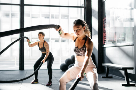 Women training with battle ropes in a crossfit box