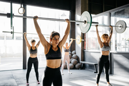 Women exercising with barbells in a crossfit box
