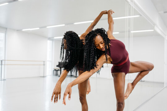 Graceful black woman dancing near mirror
