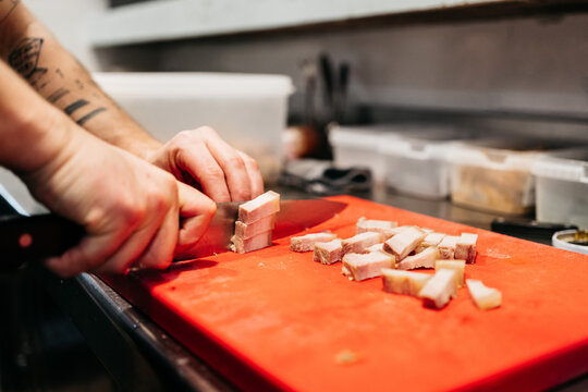 Anonymous cook cutting pork belly