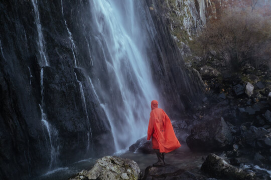 Orange man looking at a waterfall