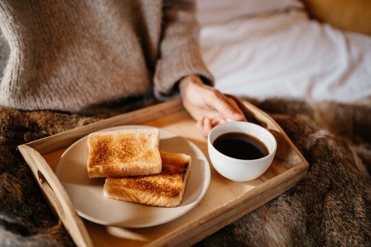 Anonymous woman having continental breakfast at bed