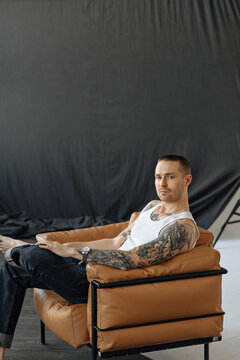 attractive young man in jeans and a white T-shirt is sitting on a leather chair and looking at the camera