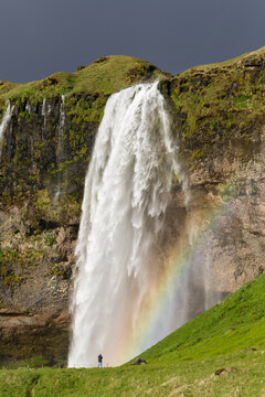 A rainbow and a tiny man taking a picture of seljalandsfoss, iceland
