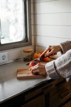 Anonymous woman cutting a tomato