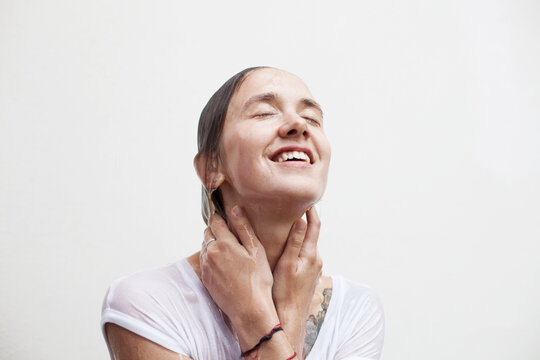 Smiling face of a young woman with flowing drops of water