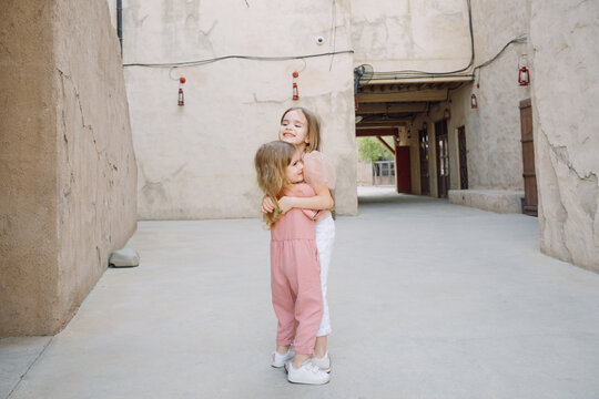 Two sisters hugging in an Arabic style district