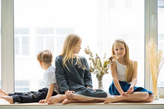 three children are sitting on the windowsill