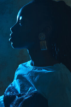 Closeup profile portrait of a black girl with golden earring sitting in a blue light in a fashionable outfit