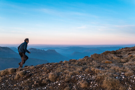 man running the rugged top of a mountain at sunset