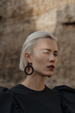 Close-up of a blonde model with massive black earrings