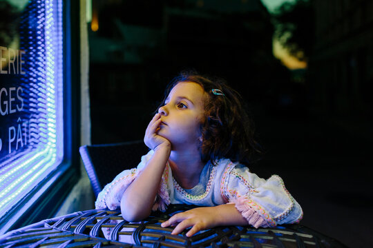 Kid sitting outside a blue neon lighted store window at night