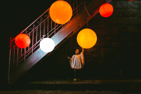 Scene of a kid under the stairs touching a big orange lamp