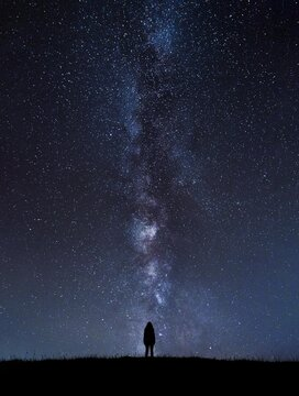 Silhouette of unrecognizable person standing under cosmic sky at night