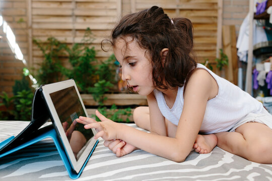 Kid looking at a tablet in a terrace