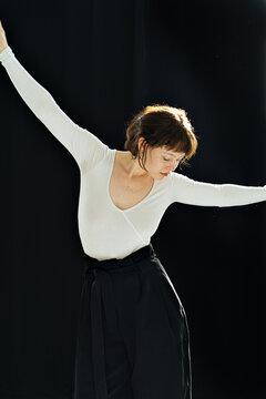 beautiful dark-haired girl dancing on a dark background