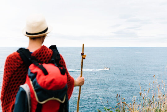 Back view of anonymous female hiker with backpack and stick standing on hill and admiring rippling sea with floating boat while resting during Camino de Santiago route in Spain