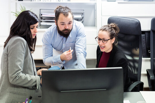 Serious young businessman and female colleagues gathering around computer and discussing business data while working together in contemporary workspace