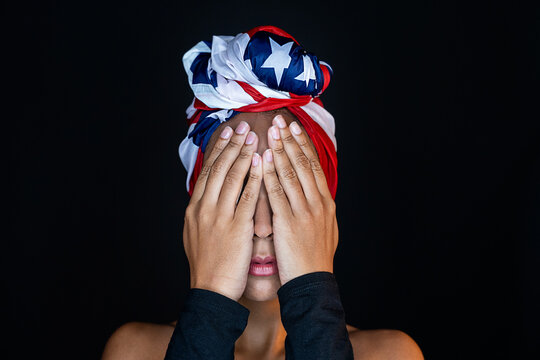 Portrait of unrecognizable scared black female wearing proudly the united states of america colors as a head wrap while covering eyes with hands on black background