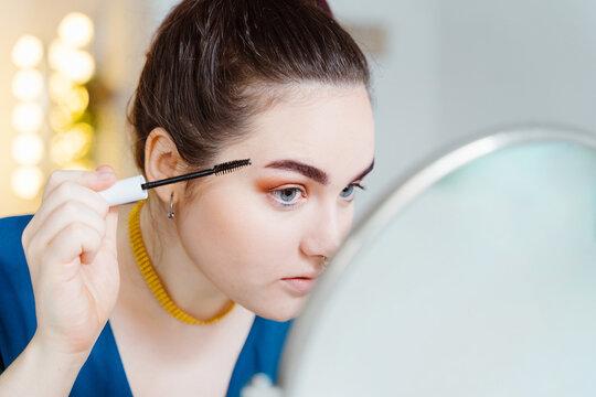 Focused female makeup artist applying mascara on eyelashes while looking in mirror in modern beauty studio