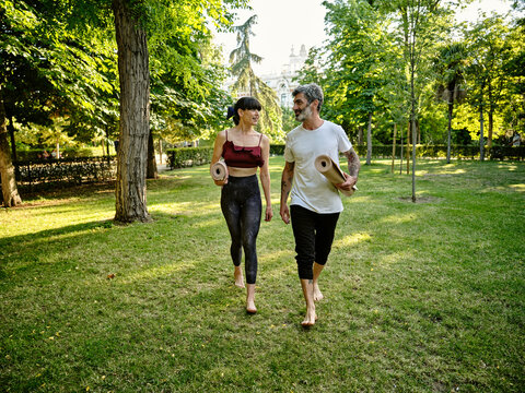Positive adult tattooed man and cheerful woman in casual clothes with rolled up yoga mats talking while walking in green park after practicing yoga together