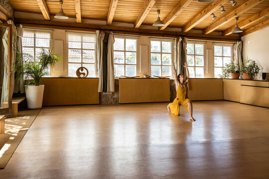 Concentrated female in long waving dressstanding barefoot in studio and practicing yoga in Anjaneyasana