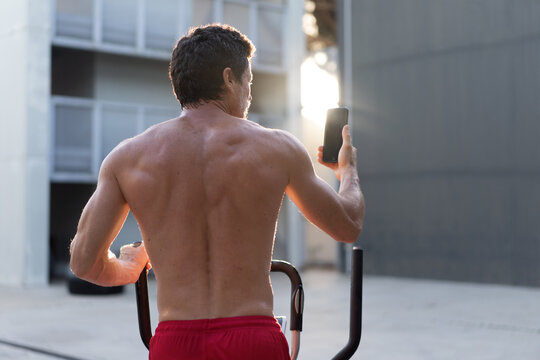 Back view of athletic male with naked torso doing exercises on stepper and taking selfie on smartphone during workout in yard