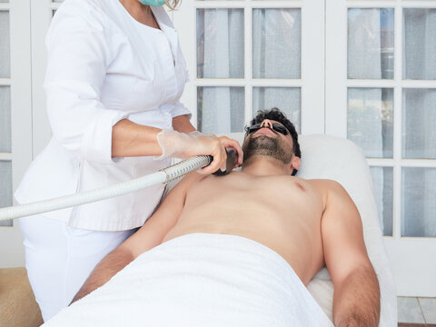 Cropped faceless master using laser apparatus on male face removing beard face during procedure in salon