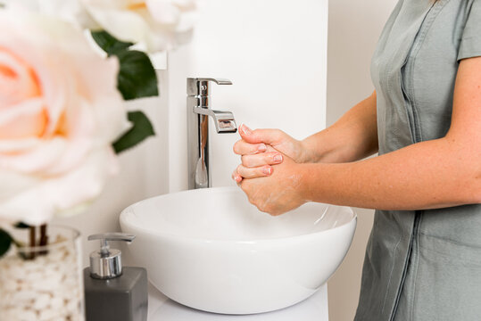 Side view of cropped female beautician doctor washing hands while preparing for treatment procedure in modern office
