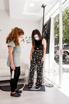 Full body young female patient cleaning shoes on sanitizing mat while entering modern clinic office during coronavirus pandemic