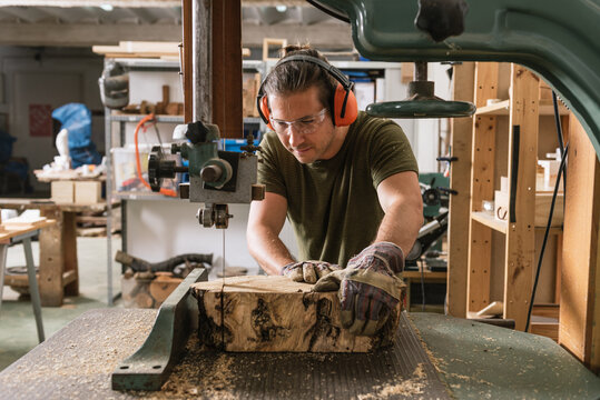 Focused male carpenter in protective ear muffs and goggles cutting piece of wood with band saw in shabby workshop