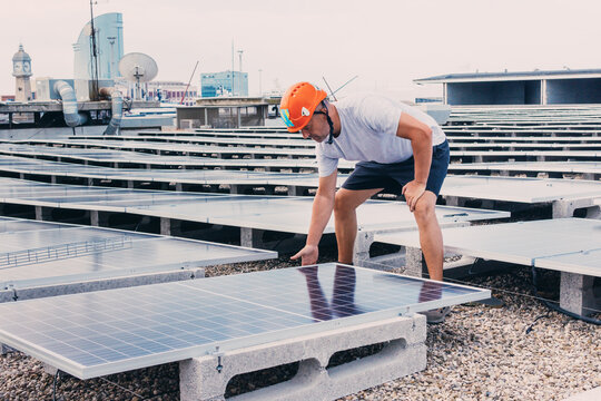 Serious male in helmet worker installing modern solar panels while working in industrial area of plant on sunny day
