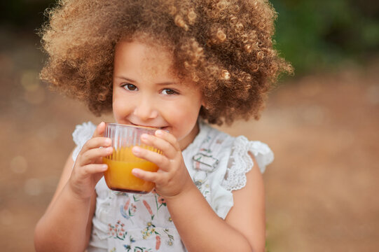 High angle of cute healthy mixed race little girl with fair Afro hair drinking fresh orange juice from glass and looking at camera against blurred nature background