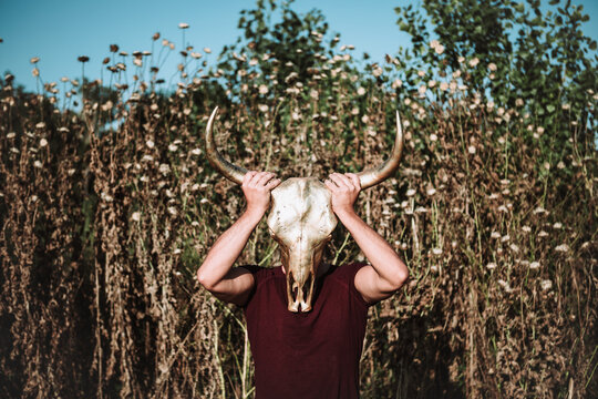 Full length of anonymous male in casual wear covering face with horn animal skull while standing in field
