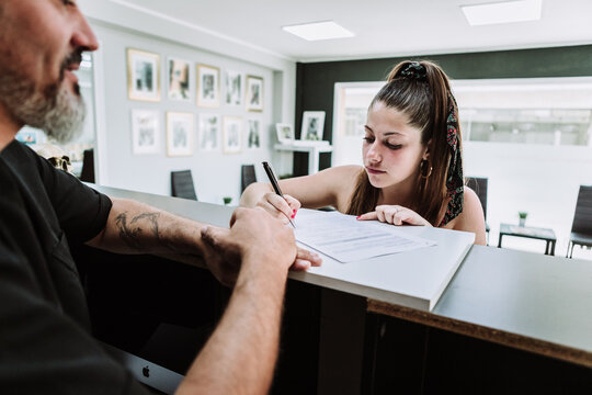 Young female standing at counter in tattoo salon and signing document before procedure