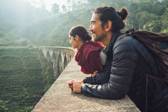 Side view of cheerful ethnic man and woman in activewear with backpacks standing contemplating views on aged stone Nine Arch Bridge among green hills in Sri Lanka